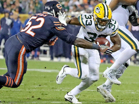 Green Bay Packers running back Aaron Jones pushes past Chicago Bears linebacker during Thursday's game at Lambeau Field.