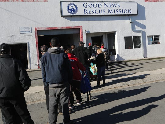 File photo - People wait in line for clothing at the Good News Rescue Mission during their 2016 Christmas banquet.