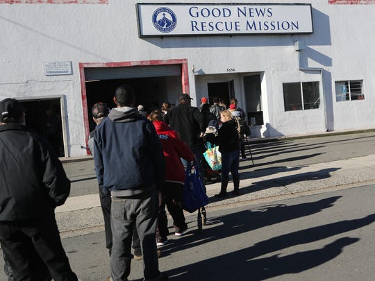 People wait in line for clothing Friday at the Good News Rescue Mission during their Christmas banquet.
