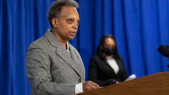 Mayor Lori Lightfoot and Chicago Public Schools CEO Janice Jackson, background, announce Sunday at City Hall that a tentative agreement has been reached with the Chicago Teachers Union to reopen schools. The proposed deal is subject to an approval vote by CTU's House of Delegates.