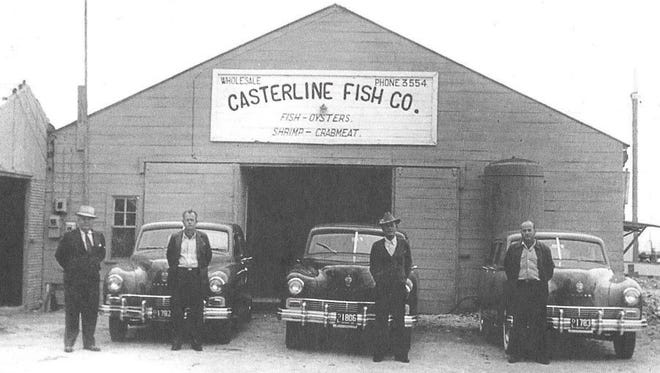 The Casterlines: L.E. Casterline (from right), Frank Casterline and Cecil Casterline, stand in front of Casterline Fish Company's building with a car salesman.