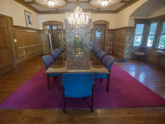 The very large dining room has tall oak paneling with