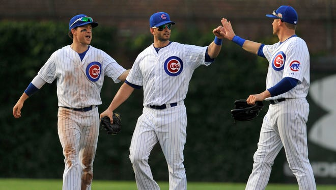 Chicago Cubs outfielders Justin Ruggiano, left, Chris Coghlan, center, and Ryan Sweeney right, celebrate after the Cubs defeated the Washington Nationals 7-2.
