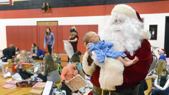 Mike Winland, as Santa Claus, holds newborn Alexander James McKamey as children open gifts on Christmas Eve during the 23rd annual Christmas on the Hill at Bishop Rosecrans High School in Zanesville. The event provides local families in need with presents for the holidays with Rosecrans students and alumni spending time with the children to find out what they want for Christmas.