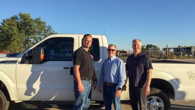 Director and fire marshal for Eddy County Fire Service Joshua Mack, senior operations superintendent for Devon Dan Werner and Eddy County Manager Rick Rudometkin stand next to the donated Ford truck.