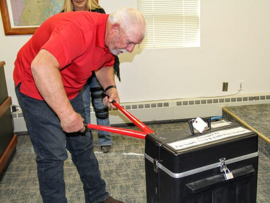 Commissioner Ronny Rardin helps break the lock of one of the precinct ballot boxes on Thursday.