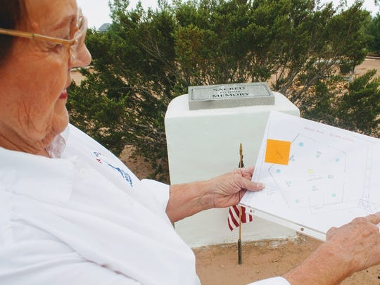 American Armed Forces Museum Vice-President Marie Wuersching holds up a blueprint of the still developing Walk of Heroes Park Friday afternoon.