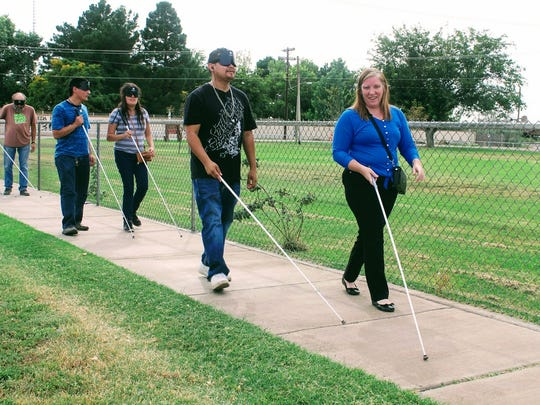 Local visually impaired residents and students walk down White Sands Boulevard Wednesday afternoon to raise awareness for White Cane Safety Day.