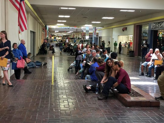Hobby Lobby employee hopefuls sit and wait until they are called for an interview outside the old Payless Shoesource inside White Sands Mall Monday afternoon.