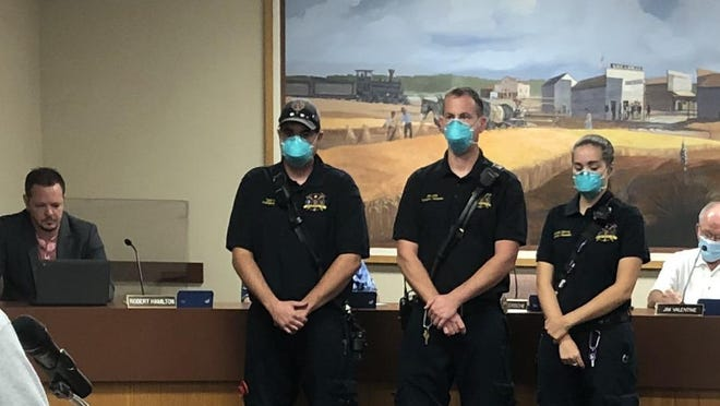 From left to right,  EMT Tyler Weiss, Paramedic Mike Clark and Paramedic Rebekah Murray, and EMT-A Sam Pacino (not pictured) receive a commendation from Assistant Fire/EMS Chief Harold Parkey, and the Wellington City Council for excellence in care of a patient.