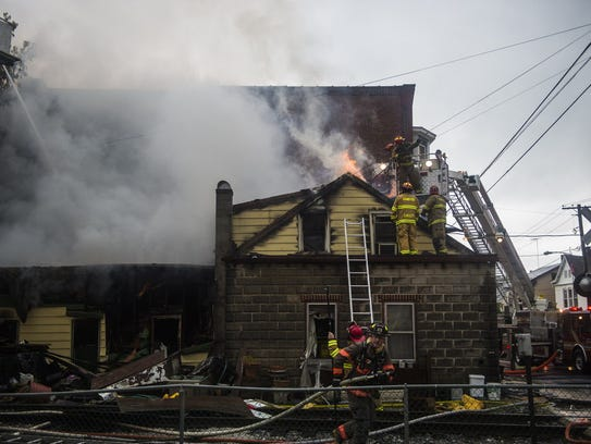 Firefighters battle flames emitting from the roof of