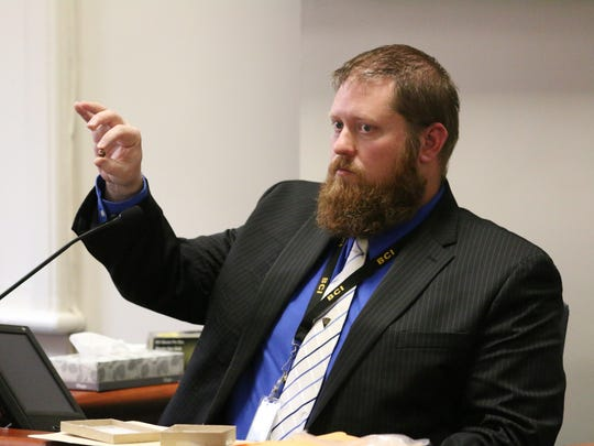 Matthew White, firearms examiner for the Ohio Bureau of Criminal Investigations, holds up a bullet he examined as part of the investigation into Timberly Claytor's shooting death May 29, 2015. He was called to testify in Jason McCrary's murder trial Thursday.