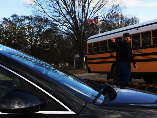 Bob Smith, 85, directs traffic so school buses can