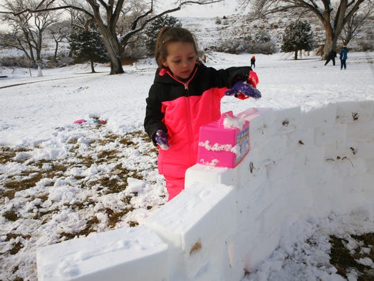 Sophie Powers places a snow brick on her igloo at Kiwanis Park in Farmington on Tuesday.