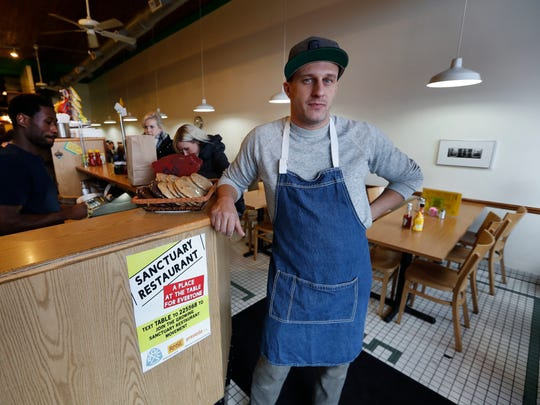 """In this Wednesday, Jan. 18, 2017 photo, Ben Hall, owner of the Russell Street Deli, poses with a sanctuary restaurant sign in Detroit. Dozens of restaurants are seeking """"sanctuary"""" status, a designation owners hope will help protect employees in an immigrant-heavy industry and tone down fiery rhetoric sparked by the presidential campaign."""