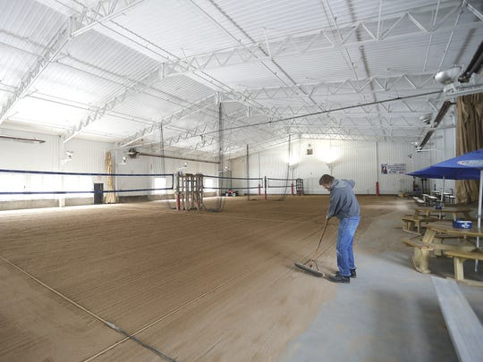 The addition of its first indoor sand volleyball courts in 1988, along with a full food menu, gave The Bar on Green Bay's east side a big boost in business. Volleyball maintenance engineer Wayne Ripley sweeps up the court edges.