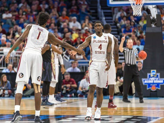 Florida State guard Dwayne Bacon (4) high fives forward Jonathan Isaac (1) during the Seminoles 91-66 second round loss in the NCAA Tournament on Saturday night at the Amway Center.