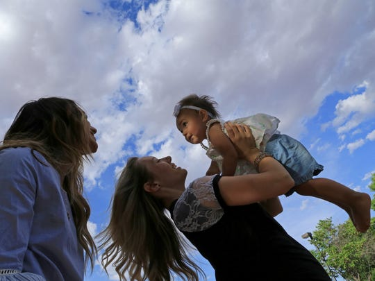 Tia Stokes watches as Chelsea Judd plays with her daughter, Giselle, on May 2 at Nisson Park in Washington City.When Chelsea faced fertility issues, Tia donated eggs for in vitro fertilization.