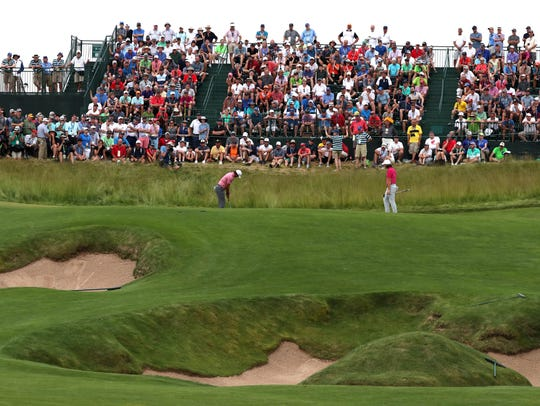 Brooks Koepka putts on the 15th hole in the third round
