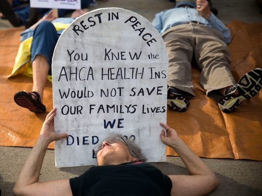 "A demonstrator holds a tombstone poster during a demonstration protesting the American Health Care Act in Market Square in Knoxville on Wednesday, June 21, 2017. Demonstrators staged a ""die-in"" holding fake tombstones and laying on the ground."
