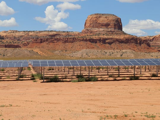 This Aug. 24, 2017 photo provided by Navajo Nation Office of the President and Vice President shows solar panels near famed sandstone buttes along the Arizona-Utah border on the Navajo Nation. The Kayenta Solar Facility is the first utility-scale solar project on the reservation, producing enough electricity to power about 13,000 Navajo homes.