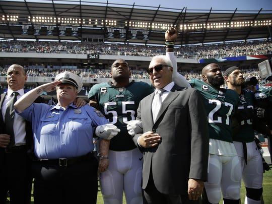 Philadelphia Eagles players, owner Jeffrey Lurie, Eagles' President Don Smolenski, and a Philadelphia police officer, stand for the national anthem before an NFL football game against the New York Giants, Sunday, Sept. 24, 2017, in Philadelphia. Eagles' Malcolm Jenkins, No. 27, raises his fist next to Lurie. (AP Photo/Matt Rourke)