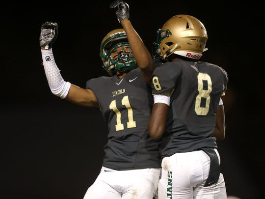 Lincoln's Marko Skarica, left, and Christopher Beard celebrate a touchdown against Godby during their game at Cox Stadium on Friday.