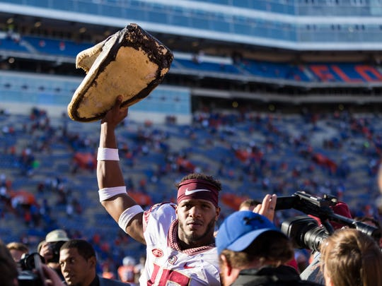 Florida State senior linebacker Jacob Pugh (16) celebrates with the gator head after his team's 38-22 victory over Florida at Ben Hill Griffin Stadium.