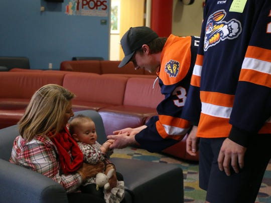 Members of the Greenville Swamp Rabbits meet a patient from the Greenville Shriners Hospital for Children.
