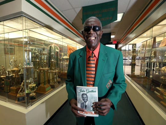 Roosevelt Wilson holds a copy of his book, a biography on legendary FAMU coach Jake Gaither, in the trophy room at Bragg Memorial Stadium on the university's campus Wednesday, Jan. 10, 2018.