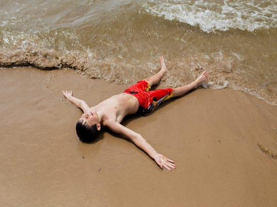 George Ellis, 10, of Conklin, lies in the sand after
