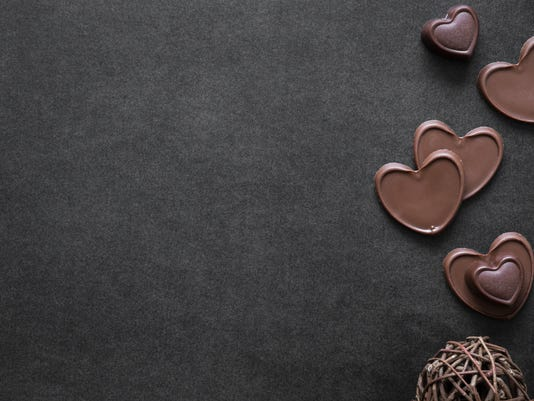 Chocolate hearts on the dark table. Enjoying a candies. Valentine's day concept. Mock up for candies offers as advertising or web background, or other ideas. Empty place for a text.