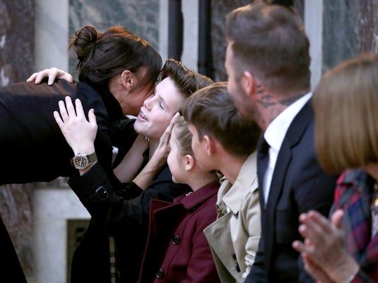 Victoria Beckham embraces her son, Romeo Beckham, seated