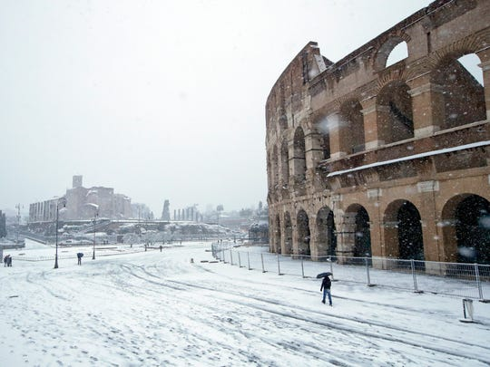 People walk along the ancient Colosseum blanketed by the snow in Rome, Monday, Feb. 26, 2018.