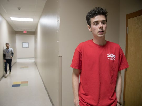 Tres Rios Service Academy teacher Noah Karvelis wears a red t-shirt and organized a day of teacher protest to highlight low pay and the state's failure to make significant efforts to address the issue.