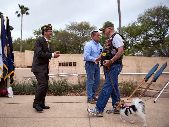 Dr. Du Hua (from left) and Martin Longoria recognize Vietnam veteran Larry Stoker, who served in the Army, and his dog, Kenpo, during the Vietnam Veterans Day Ceremony hosted by the Veterans Band of Corpus Christi at the Fallen Heroes Memorial at the Nueces County Courthouse on Tuesday, March 27, 2018.