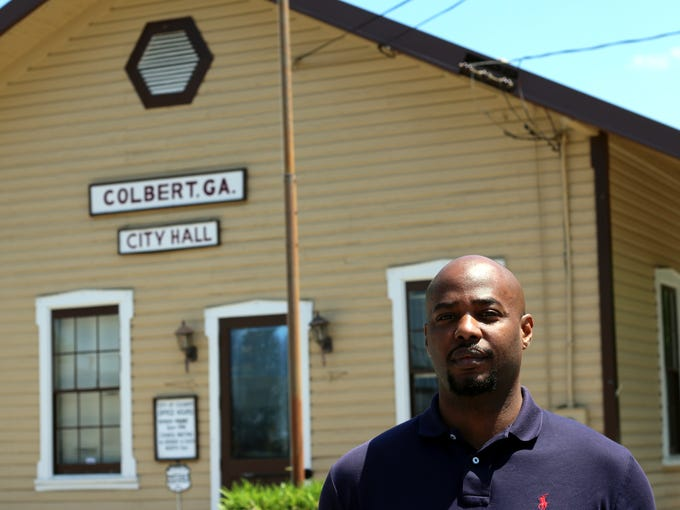 Evan Lewis stands in front of City Hall in Colbert,