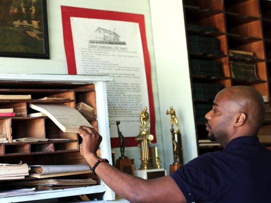 Evan Lewis browses old documents inside the small history museum at Colbert City Hall. No records related to his great-grandfather Lent Shaw were found.