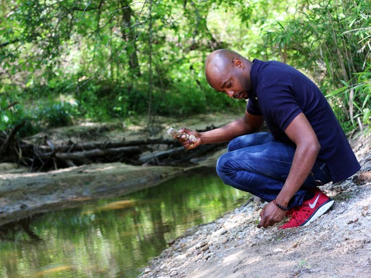 Evan Lewis picks up rocks along the Mill Shoal Creek bed in Colbert, Georgia. Lewis took some rocks as mementos because the creek is near where his family lived in 1936.