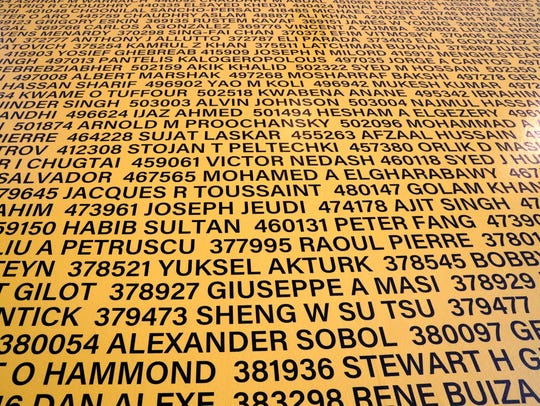 Names on the wall are part of the 5000 Rides artwork on exhibit at Elsa's on the Park. This is one small section showing names and operator license numbers of New York City cabbies.