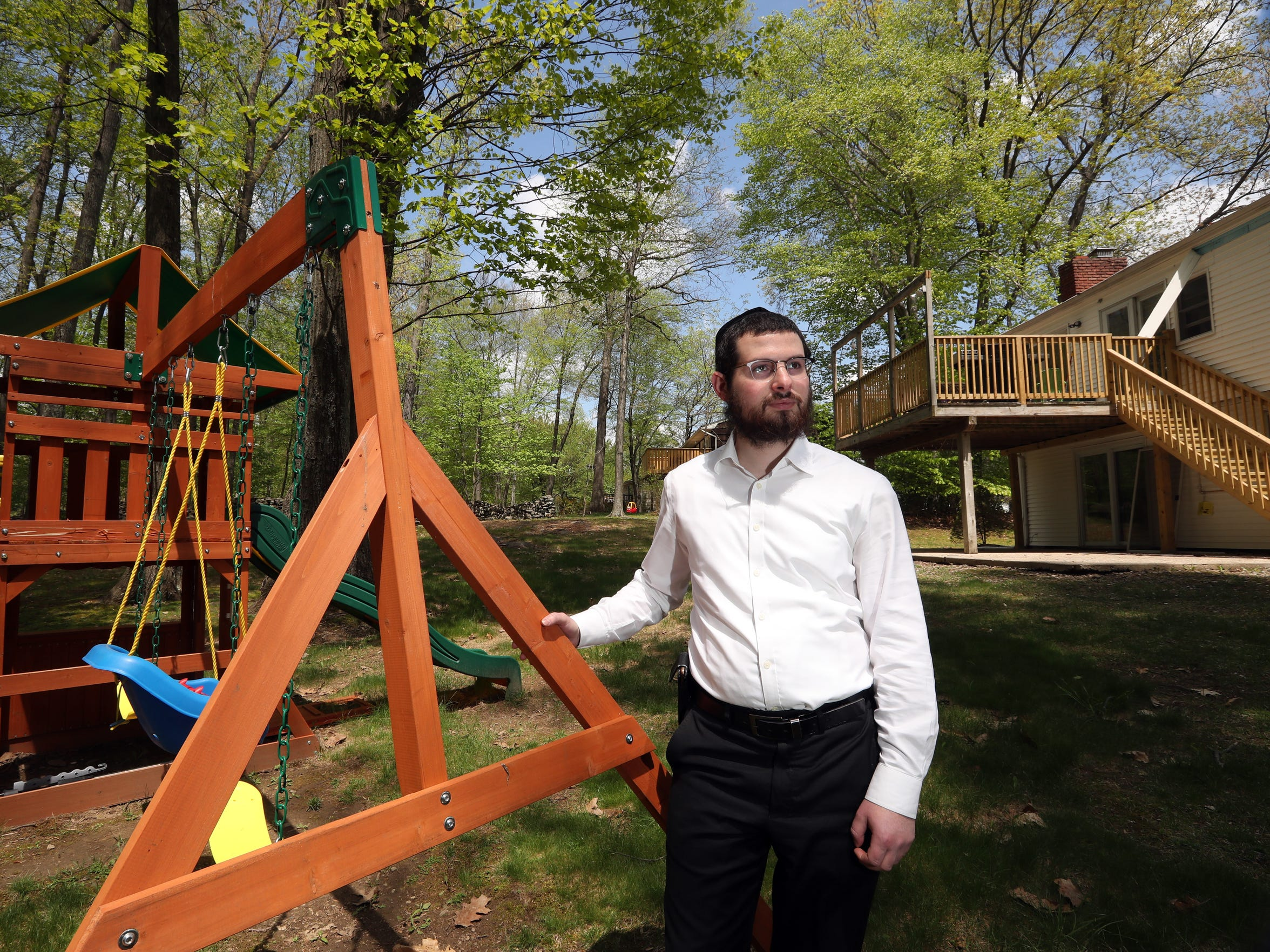 Nathan Unger, 29, stands in the backyard of his home in Airmont on May 8, 2018. Unger, who lives with his wife and two children, says he's been denied permits to expand his house even though he filed before the village's building moratorium was enacted. Building Inspector Lou Zummo says that Unger's original application was incomplete and that he didn't update the paperwork before the moratorium went into effect.