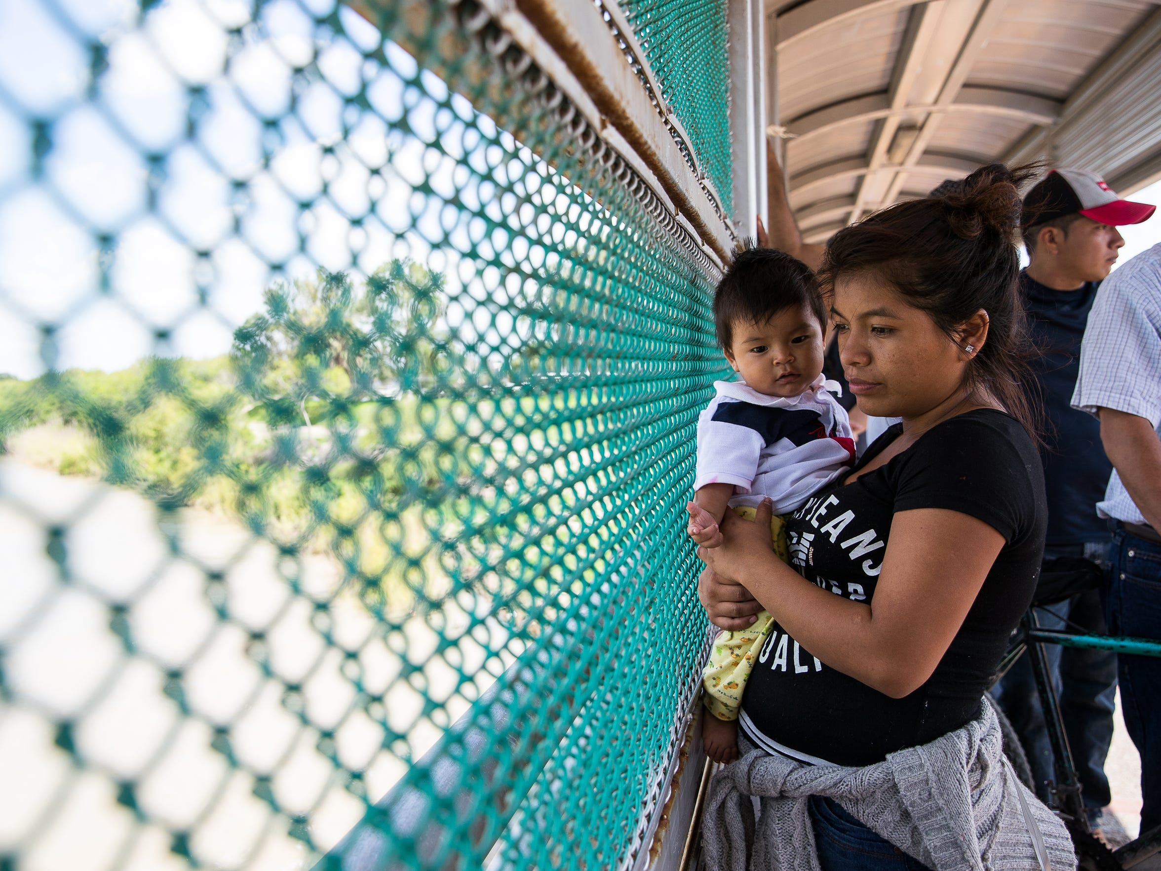 A Guatemalan woman and her child, who have been waiting since 6 a.m. seeking asylum, wait on the Mexican side of the international bridge to enter the U.S in Brownsville, Texas, on Wednesday, June 27, 2018.