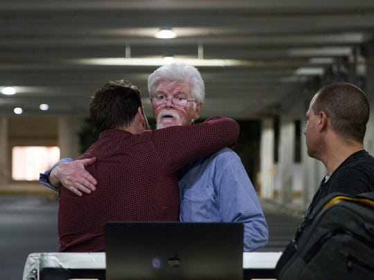 Capital Gazette reporters Pat Furgurson, center, and Chase Cook hug at a makeshift office June 28, 2018, in a parking garage of a mall in Annapolis, Md., during coverage of the fatal shootings in their newspaper's newsroom earlier in the day.