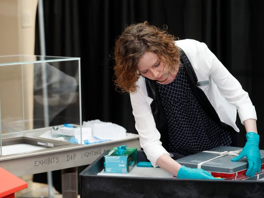 "Kimberly Kronwell, registrar of exhibits and loans to the Colorado History Museum, opens the case containing the ""Holy Grail"" of baseball cards, a 1952 Topps Mickey Mantle that is valued at more than $10 million, to put on display as part of baseball memorabilia exhibit at the Colorado History Museum Monday, July 16, 2018, in Denver. The pristine card, one of three known to still be in existence, is owned by Denver lawyer Marshall Fogell."