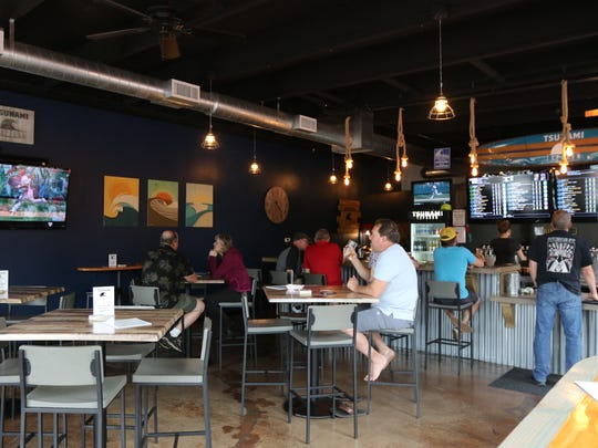 Blue walls, rope pendant lights, and graphic prints of the ocean give Tsunami taproom a beachy feel.