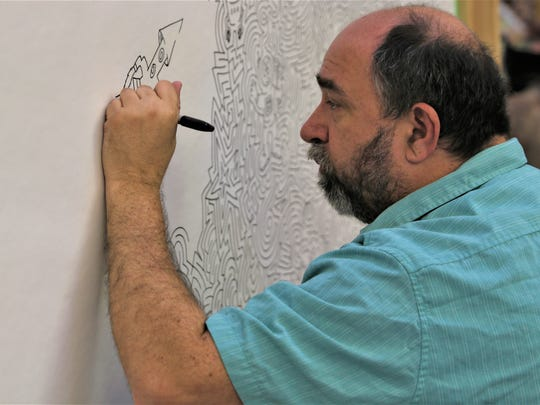 Maze artist Joe Wos draws a rocket ship as part of a maze mural with a space theme that he created Tuesday at the Farmington Public Library.