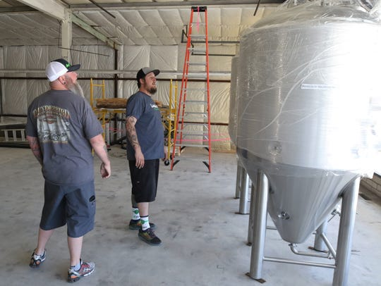 Brad Foley, left, and Brandon Beard examine the fermenters