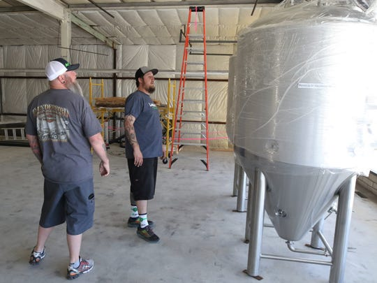 Brad Foley, left, and Brandon Beard examine the fermenters that were delivered recently to the soon-to-open Lauter Haus Brewing Company in Farmington.