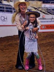 Mattie Eddleman, 17, of De Leon, laughs helping Summer Smith, 8, of Abilene during the Cavender's Special Kids Rodeo and Party Wednesday at the Coliseum.