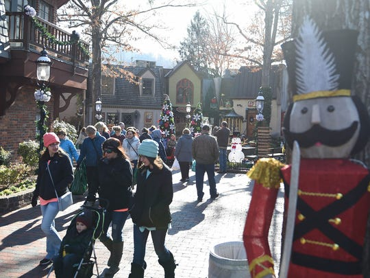Tourists visit The Village as downtown Gatlinburg, Tenn. reopens to the public, Friday, Dec. 9, 2016. Over 2,000 structures were destroyed in the area and 14 people killed after wildfires went through the area on Nov. 28th.